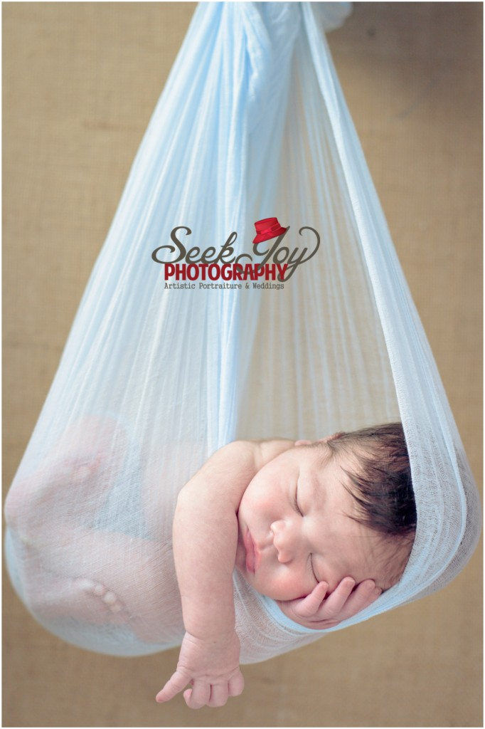 newborn hanging in blue cloth