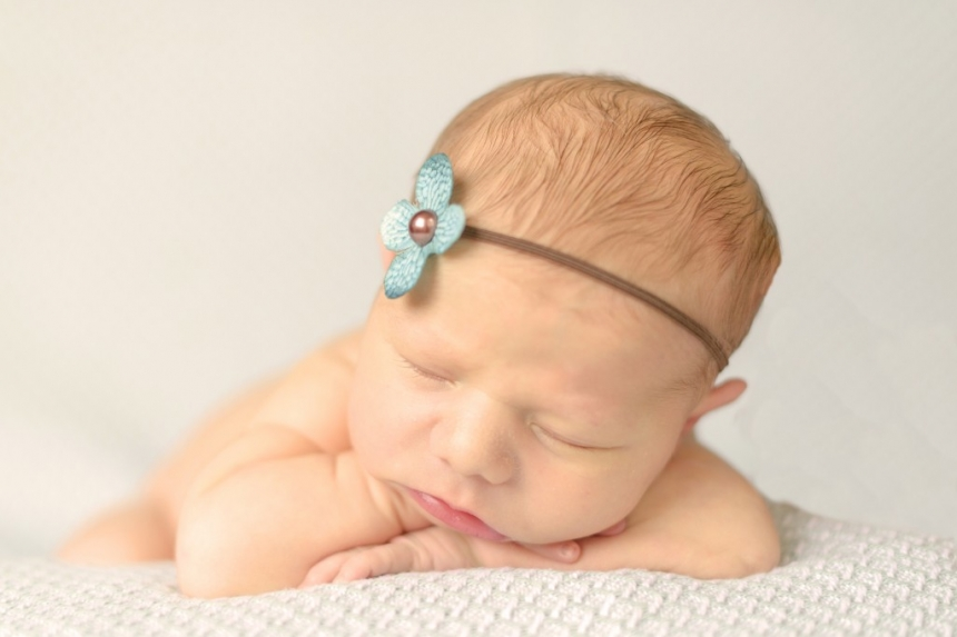 newborn girl with teal flower headband and head on hands pose