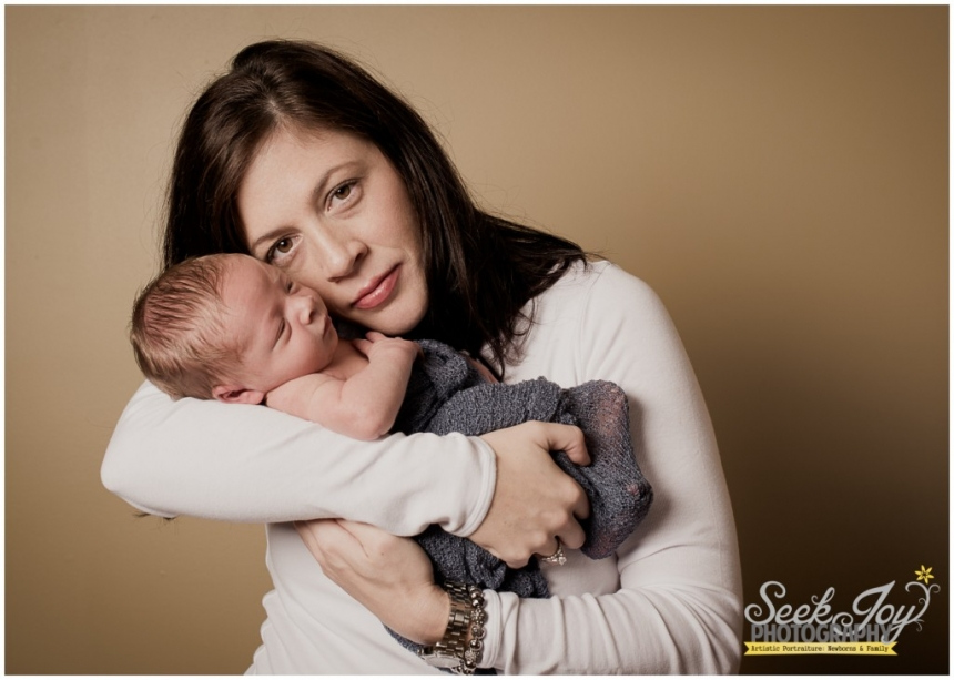 indoor portrait of mother holding newborn son closer to her face