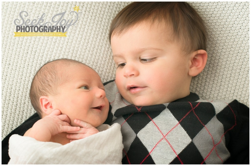 toddler and newborn brothers looking at each other