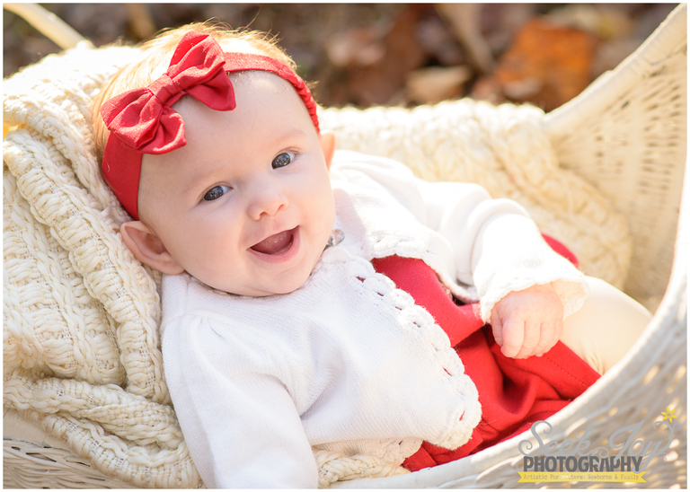 Christmas photo of happy baby girl with red bow