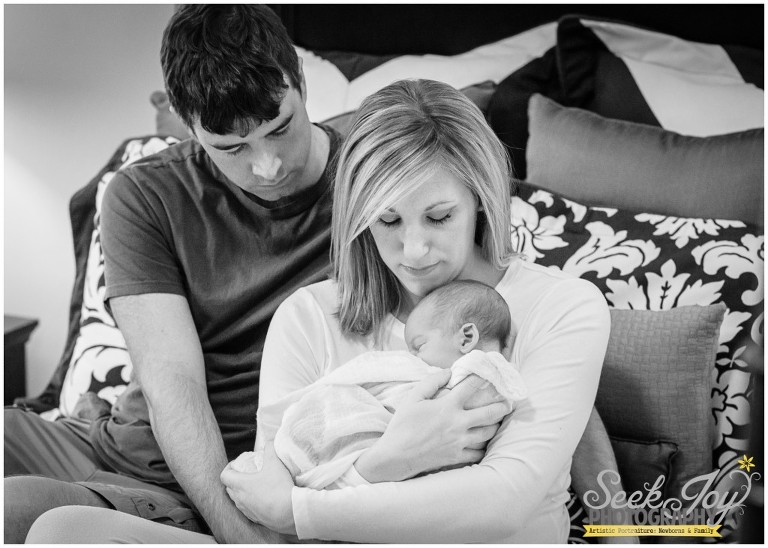parents sitting on bed holding new baby