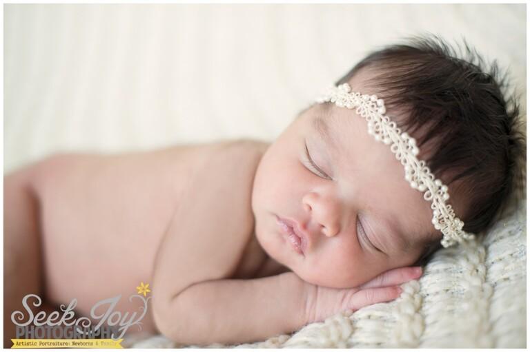 baby girl sleeping on cream blanket