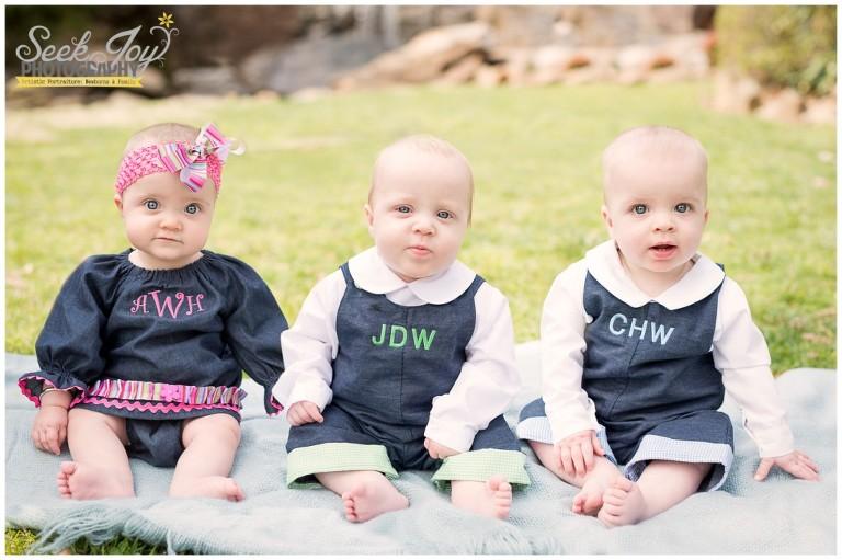 triplet siblings sitting up in the park