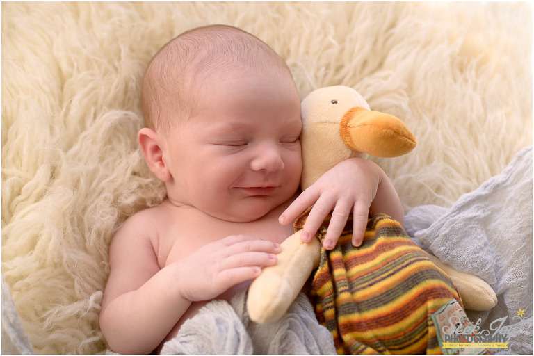 baby holding stuffed duck