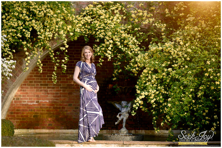 pregnant woman standing by fountain